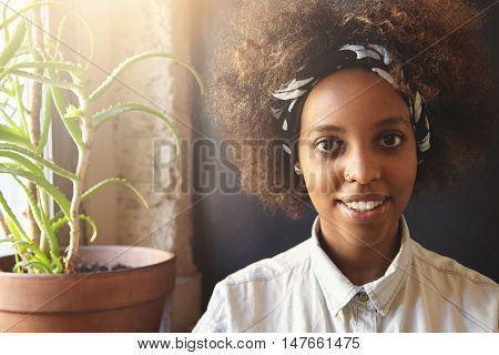 Hipster Dark-skinned Female With Facial Piercing Relaxing Indoors, Sitting On Windowsill With Aloe P