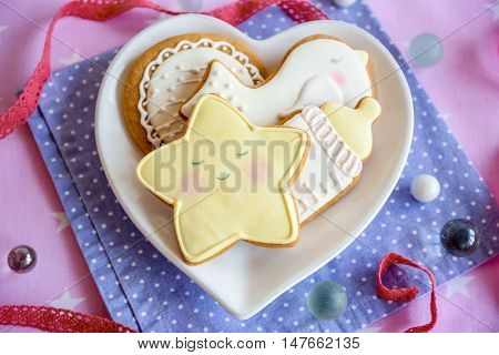 Baby glazed cookies in heart shape plate on decorated table
