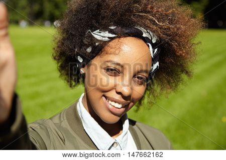 Young Stylish Woman With Afro Haircut Wearing Black Bandana, Taking Selfie, Holding Mobile Phone Or