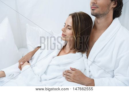 Most tender embrace. Beautiful girl lying with closed eyes in arms of her boyfriend, spending time in spa together