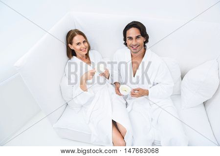 Having some fun today. Top view of man and woman sitting on white couch in spa center and looking in camera, smiling