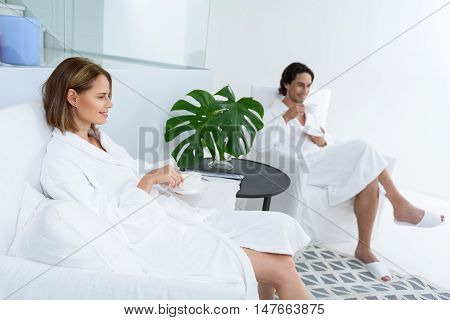 Taking relaxation to another level. Adult man and woman in white terry robes sitting in chairs in spa and enjoying their vacation, drinking tea