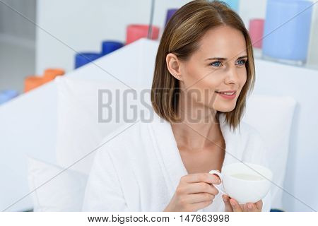 Take day just for yourself. Shot of young woman in white bathrobe drinking cup of coffee at day spa