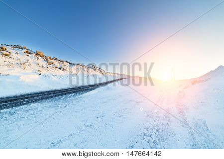 Icy winter road deicing sprinkled with black sand. Landscape with the rising sun.