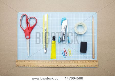 concept:stapler,glue,scissor,cutter,tape,pen,pencil,clip,ruler,rubber, cutting mat,ruler and color pencil on brown paper background.Top view