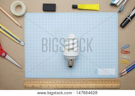 concept:stapler,glue,scissor,cutter,tape,pen,pencil,clip,ruler,rubber, cutting mat ,lamp,crumpled paper and color pencil on brown paper background.Top view