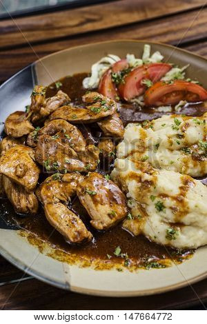 chicken breast with brown gravy sauce and mashed potato meal