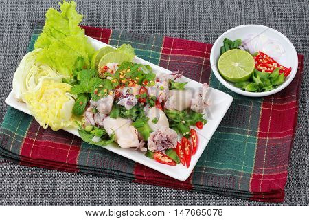 Spicy and sour mixed herb salad with squid wrap minced pork . Side view.
