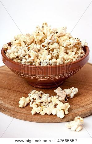 Wooden cutting board clay bowl full of popcorn some popcorn scattered.