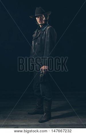 Menacing Vintage 1900 Cowboy Standing With Revolver. Studio Shot Against Dark Background.