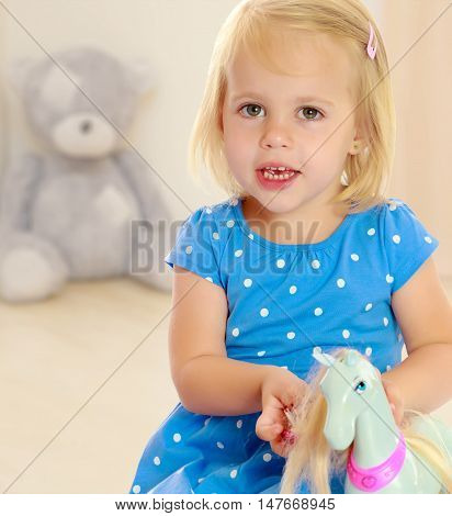 Cute little blonde girl playing with a toy horse. Girl wearing a blue dress with polka dots.In the background children's room where the sitting Teddy bear.