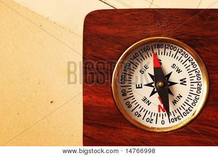 Antique wooden compass over old map background