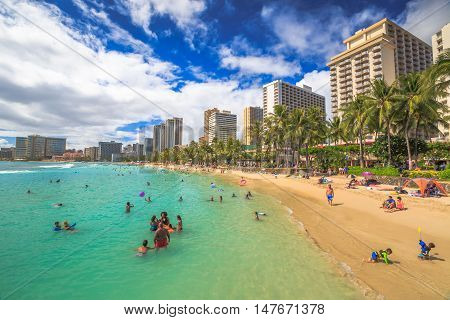Waikiki Oahu Hawaii - August 27 2016: children and families in the crowded Kuhio Beach also called The Ponds because bounded by concrete walls that have created a calm salt water swimming pool.