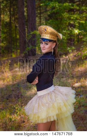 Image of a beautiful girl in uniform cap in the forest