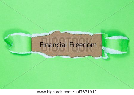 The text Financial Freedom appearing behind torn paper.