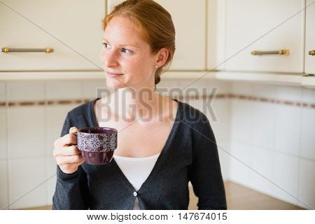A casual young woman with a cup of coffee or tea looks to her side as she relaxes in her kitchen.