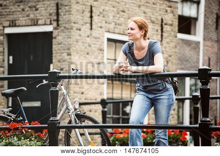 Casual female tourist rests on a bridge next to a bicycle in an old town.