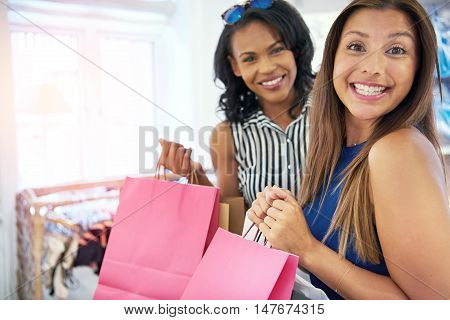 Happy young female shopper grinning at the camera as she spends a relaxing day shopping with a friend in a clothing store