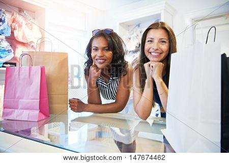 Two attractive female friends shopping together in a clothing boutique leaning on the counter with their packages waiting to pay