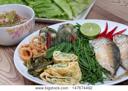 Close up of deep fired mackarel,vegetable omelet,pork rind,pickle lettuce,green lemon,red chili and boiled of eggplant,lentils,acacia and green chili dip as