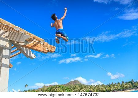 Waikiki Oahu Hawaii - August 27 2016: a boy jumping off the Waikiki Pier between Kuhio Ponds and Queens Beach two sections of Waikiki Beach. On background skyline of Diamond Head State Monument.