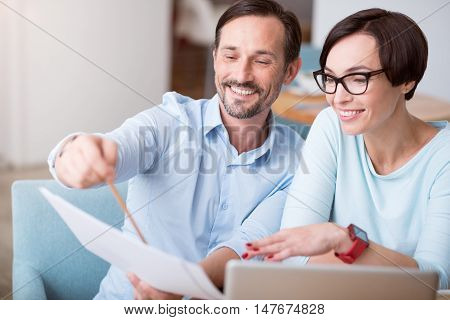 Perfect team. Cheerful and content businesspeople using laptop and holding documents