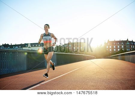 Fit athletic young woman running across a bridge backlit by the early morning sun with copy space in a health and fitness concept