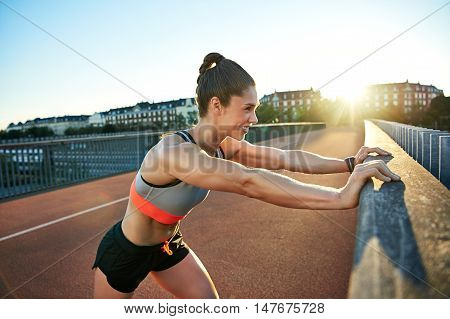Smiling muscular jogger presses against railing as she stretches her legs before running