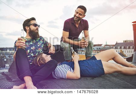 Woman laying in lap of bearded man near friend as they laugh and talk together on roof in European city