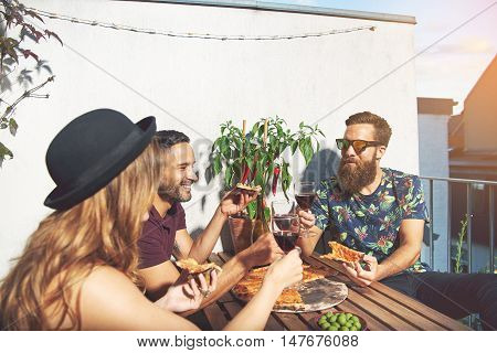 Man in sunglasses with beard raises his glass to toast with friends while seated at wooden table on their apartment patio