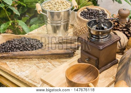 Coffee beans and coffee grinder and cup of coffee on wooden table
