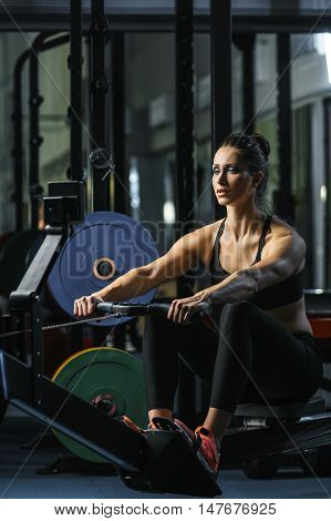 Concept: power strength healthy lifestyle sport. Powerful attractive muscular woman fitness trainer do workout on indoor rower at the gym