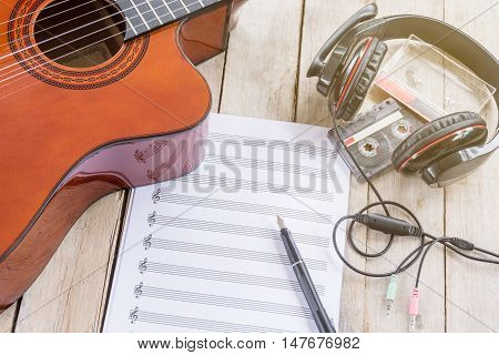 Acoustic guitar, music paper, big earphone, fountain pen, tape cassette on wooden table