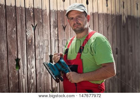 Male worker with vibrating sander standing in front of old wooden fence - about to scrape the cracked paint