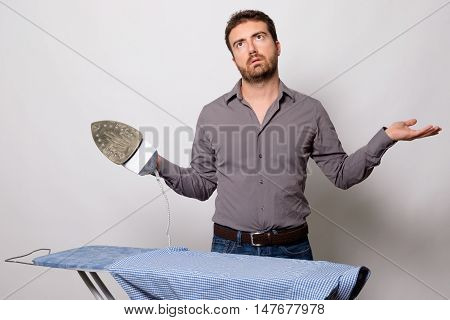 Bachelor is very bored by ironing his shirt