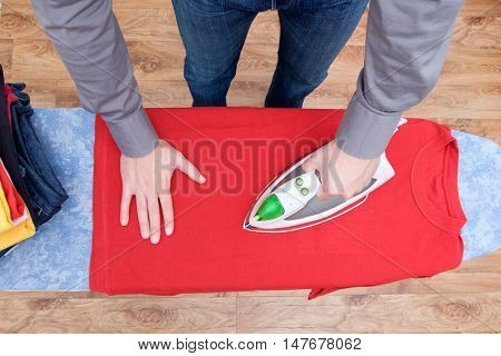 Man ironing his various clothes  close up