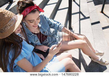 pretty women smiling and looking into a smartphone