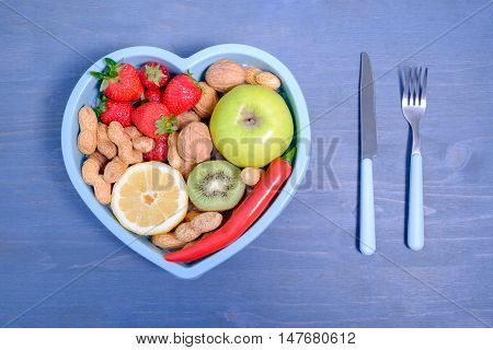 Heart shaped dish with vegetables isolated on blue wooden background