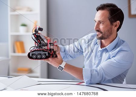 New creation. Satisfied robot inventor admiring his scientific work