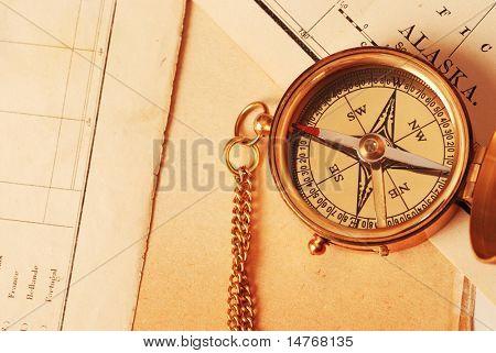 Antique brass compass over old Alaska map