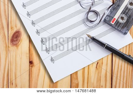 music paper, fountain pen, tape cassette on wooden table flat lay