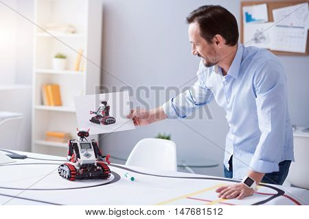 Satisfied. Scientist looking at the picture of a robot and the real machine. Both items looking alike.