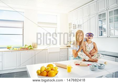 Adorable mother and daughter in floral patterned dress and purple eyeglasses laughing together in kitchen with bright white walls and windows