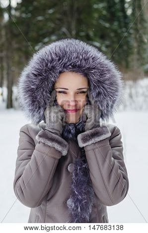 Beautiful woman in winter jacket with fur hood having fun making a funny face with Asian eyes