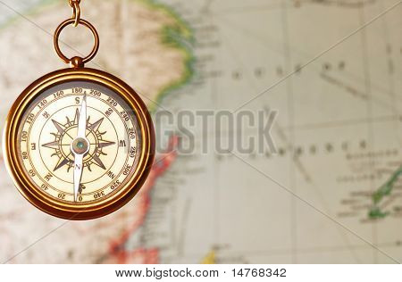 Antique brass compass over map background