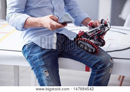 Business time. Man texting a message while holding a droid on his laps