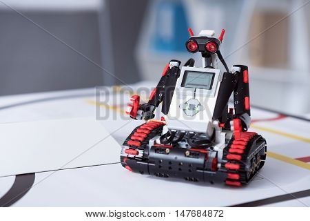 Brand-new life. Black, red and grey robot with funny ocular waiting for his first task