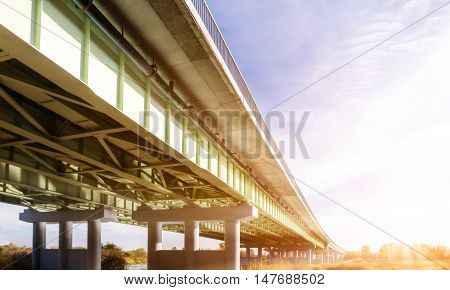 Perspective view of an overpass in front of the sun.