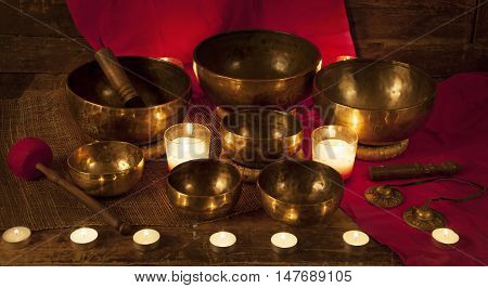 Set of Tibetan singing bowls and bells with burning candles on a red background