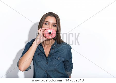 Cute girl is having fun with doughnut. She is covering her mouth with it and looking forward playfully. Isolated and copy space in right side